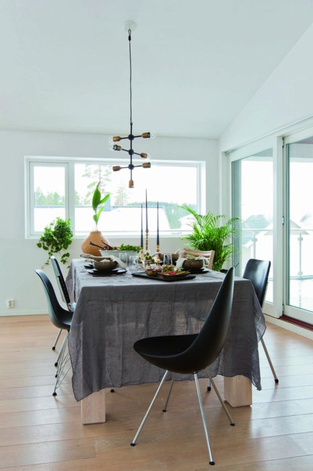 Husets hjerte. Anna og familien bruker ikke så mye tid på kjøkkenet, men spisebordet er et samlingspunkt. Store vinduer og direkte adgang til uteplass gir en deilig frihetsfølelse. Spisestolene er fra ulike bruktmarkeder, Living og Fritz Hansen. Taklampen Molecular er fra House Doctor.
