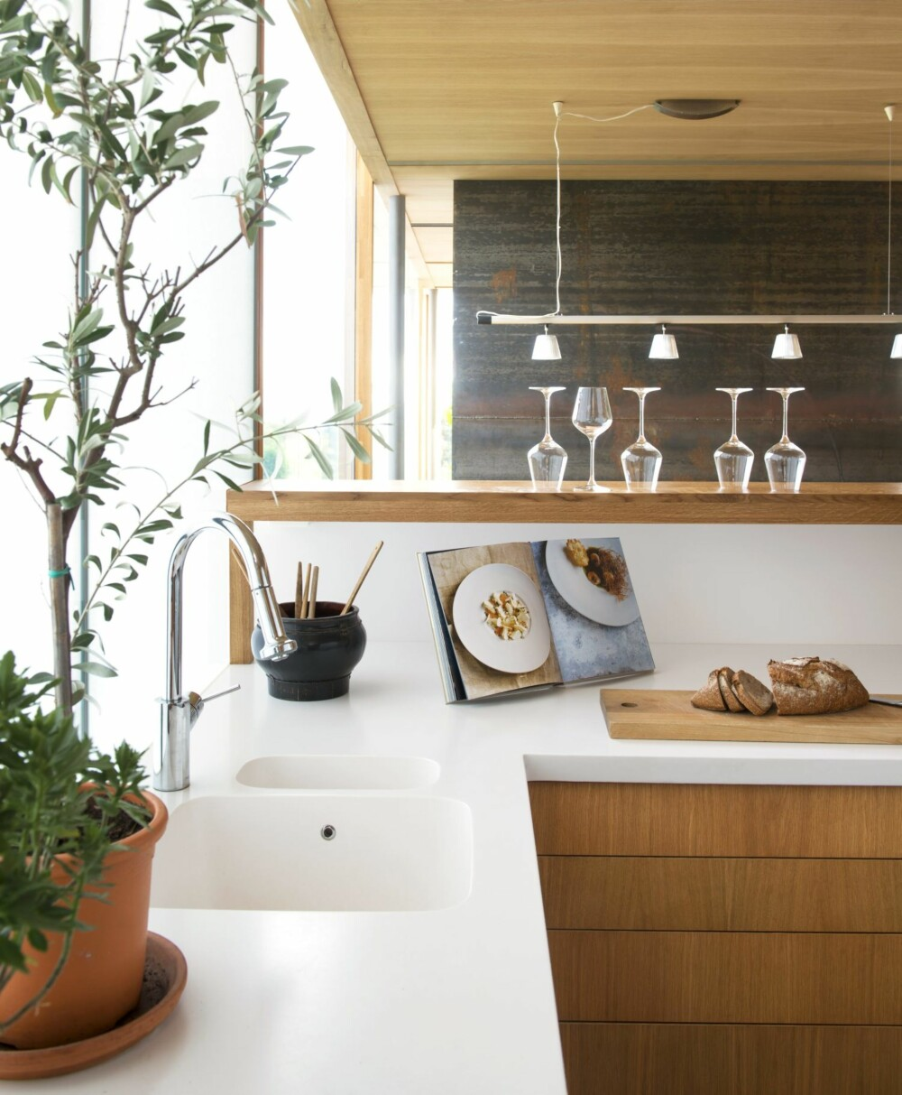 BLØTT LYS, HARD BENK: Benkeplaten er i Corian, et komposittmateriale som er nesten like sofistikert som veggpanelene. - Det er hvitt, glatt, og renslig. Jeg kommer aldri til å velge noe annet sier beboeren. Kjøkkeninnredningen er fra Country Kitchen & Interiors. Styling: Juni Hjartholm.