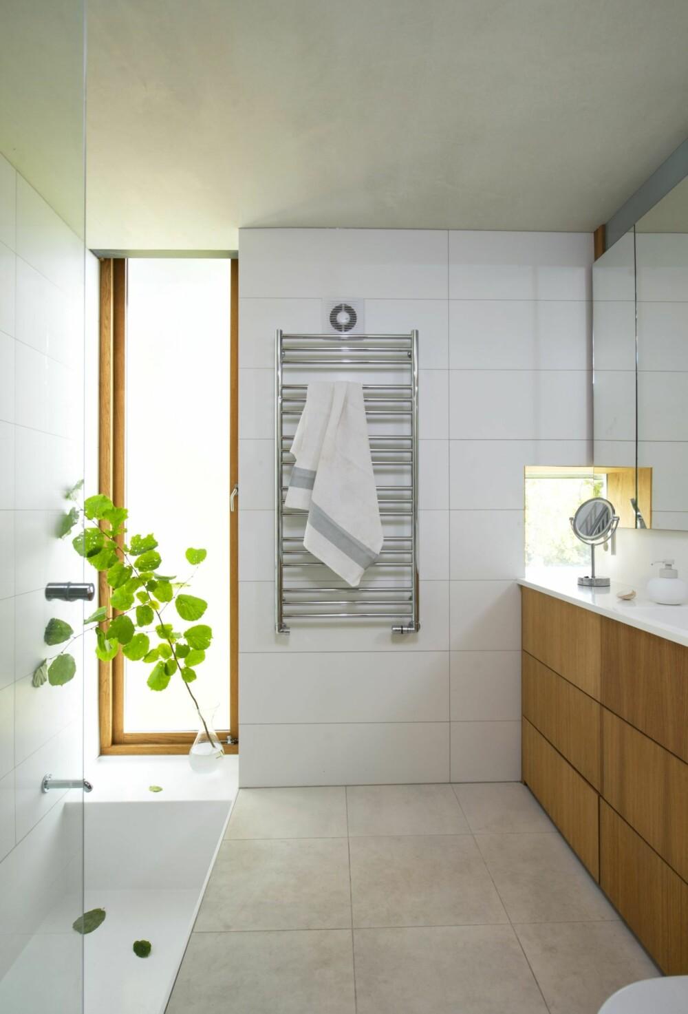 LUR LØSNING: Det litt kantete badekaret er plassert under det smale, høyreiste vinduet. Glasset er frostet for å hindre innsyn uten å stenge ute dagslyset. Eikeinnredningen er interiørets røde tråd. Styling: Juni Hjartholm.