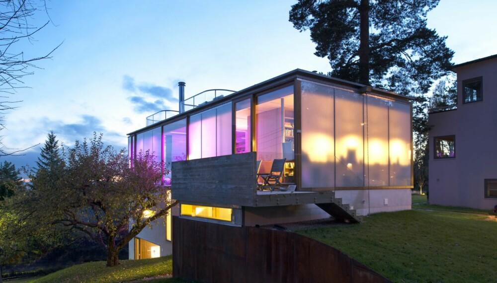 LYSENDE VEGGER: Huset lyser som en lanterne om kvelden. Den integrerte led-belysningen gjør det mulig å variere mellom hvitt og farget lys, deriblant rosa. Huset er bygget i randsonen av en tomt der det står et en autentisk funkisvilla fra før. Det nye byggets slektskap med det gamle kan spores i form og i enkelhet. Samtidig forteller materialbruken at dette er et bygg av i dag. Den majestetiske furua og det gamle epletreet forankrer nybygget til tomten og skaper en fornemmelse av at det alltid har stått et hus her.