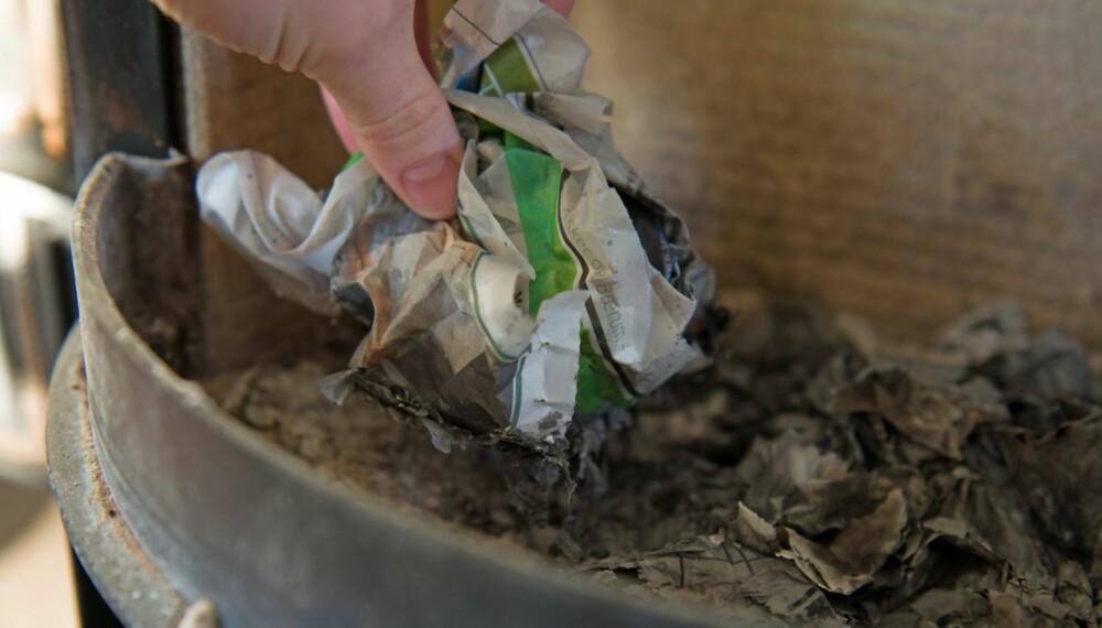 BRUK ASKE TIL Å FJERNE SOT: Fuktet avispapir dyppet i aske kan brukes til å rense ovnsdøren for sot.