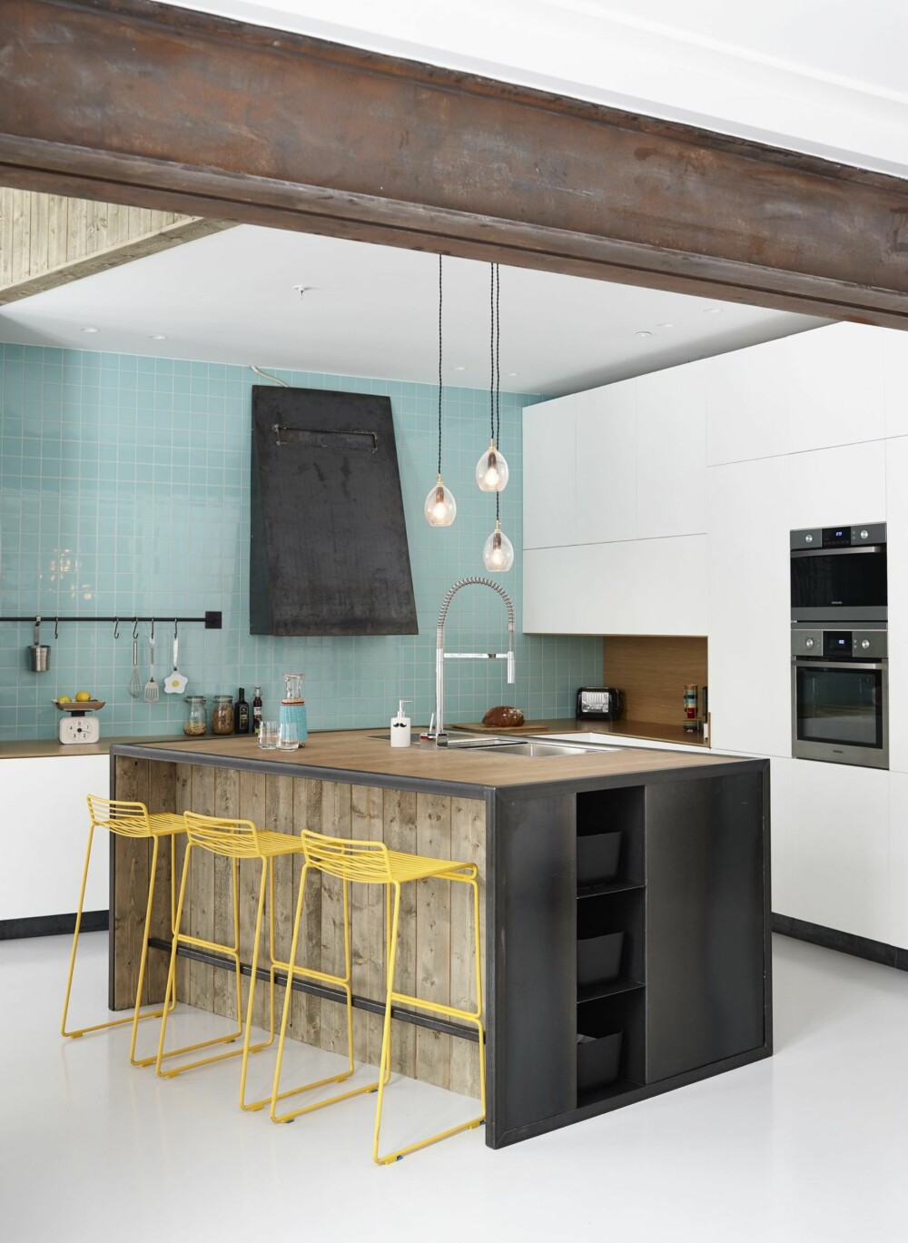 KONTRASTERENDE MATERIALER: Kjøkkenøya er produsert av Bolt Metall. Innredningen er dimensjonert for røff bruk. Benkeplaten er i bambus, og hjørner og hyller er i stål. Innredningen er designet av Wood Arkitektur + Design. Barstolen er fra Hay. Veggen er kledd med fliser fra Vitra.