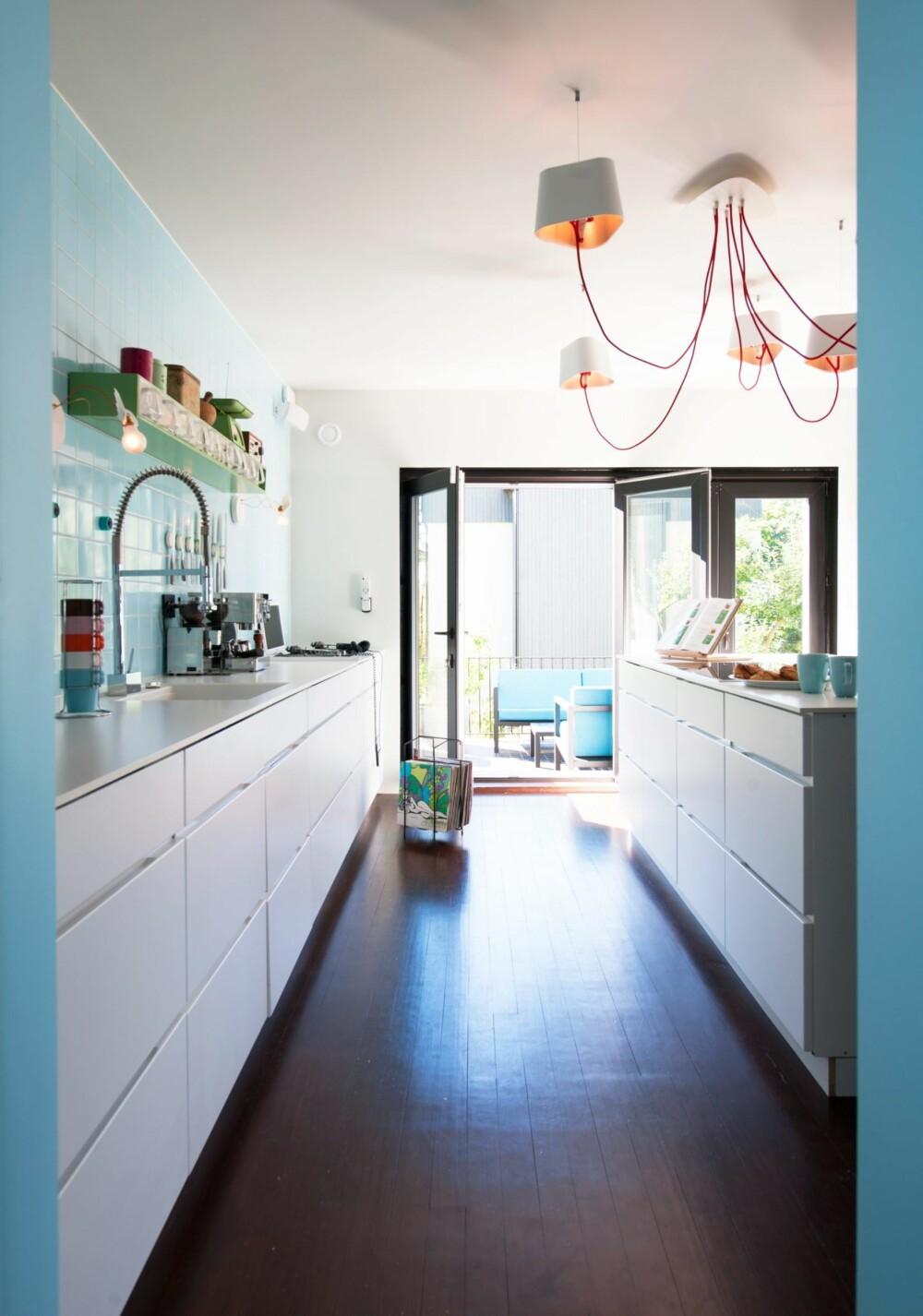 ÅPNET MOT UTEPLASSEN:  I enden av kjøkkenet er vinduene mot terrassen skifet ut med foldedører slik at man har god kontakt med miljøet utenfor. Kjøkkeninnredningen er fra Kvik, taklampen fra Designheure.