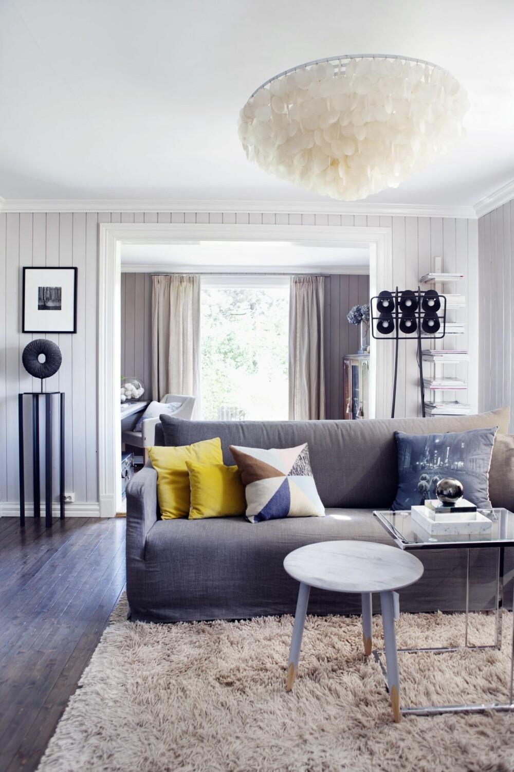 DELIKAT: Brede døråpninger mellom stuene bidrar til følelsen av luft og rom. Ved å velge en litt mørkere nyanse (fargekode S2002-R50B) på det ytterste rommet oppnås en fin dybdefølelse. Høyblanke lister blir en elegant kontrast til det malte rupanelet og det beisede gulvet. Sofa fra Hoffz/Edda Interiør, glassbord fra BoConcept/Skeidar, trebord Hoof fra &Tradition. De gule putene har Birgit sydd selv, strikkeputen er fra Bolina, puten med svart-hvitt trykk fra Edda Interiør. Pidestall fra ShiShi, figur fra Konzept H-P, stålampe fra Seletti. Taklampen er fra Jane Doe, en butikk som nå er nedlagt. Styling: Tone Kroken.