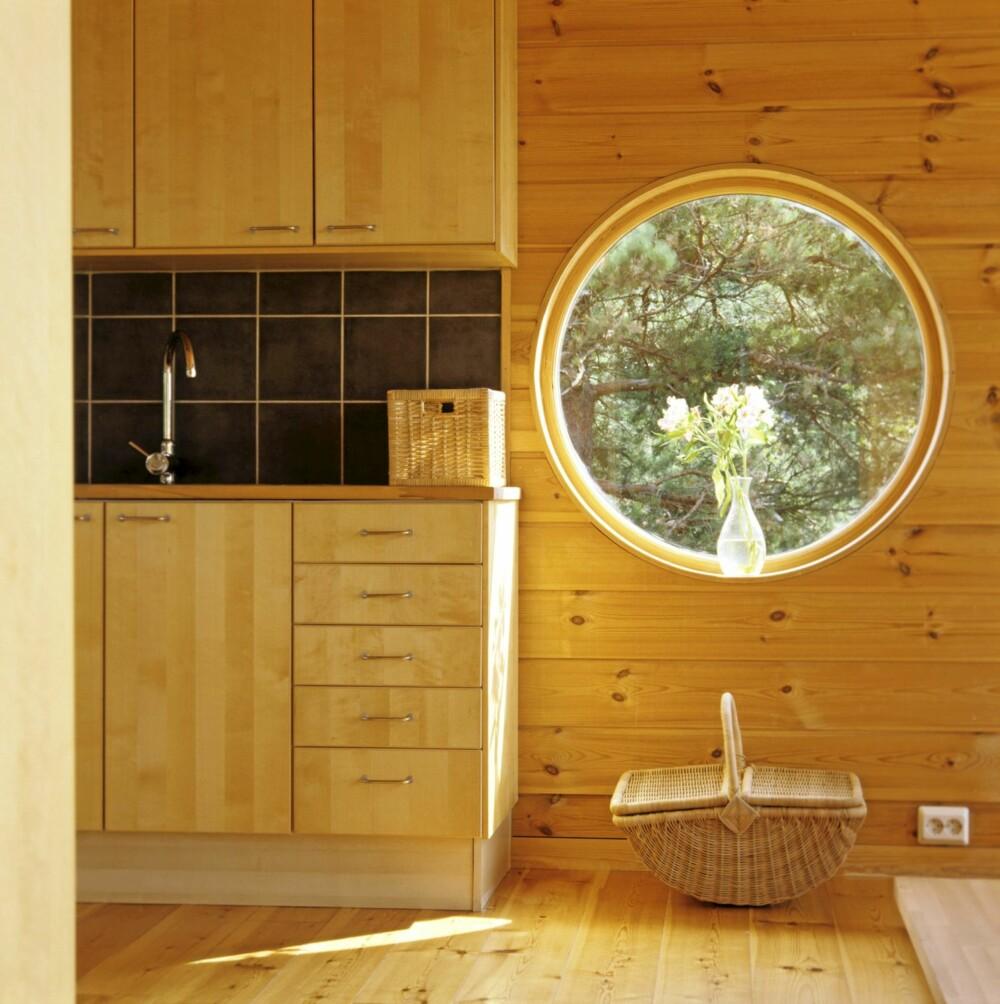 SLIPP INN MORGENLYSET. Det store, runde vinduet er kjennemerket på denne skjærgårdshytta og åpner stuen for morgensolen. Merk, vinduet er uten forstyrrende listverk.