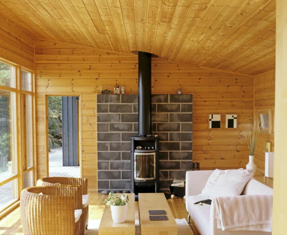 HARMONISK MED TRE: Stuedelen er den største av de tre delene av hytta. Brannveggen av Leca-blokker er laget ekstra stor. Scan-peis og Kurvstoler fra Skeidar. Panelveggene får stå ubehandlete.
