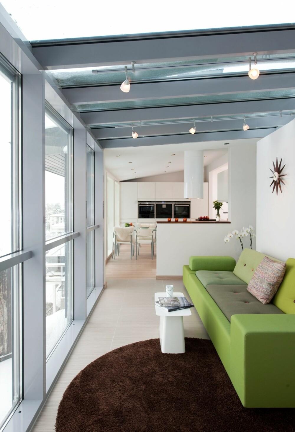 LYSSKINNER. Skinner i taket med bevegelige lyspunkter er en god investering. Her er sofaen plassert med sitteplassene mot utsikt og dagslys. Takvinduer gir også ekstra dagslys inn i rommet. På kveldstid gjør lysskinnene jobben.