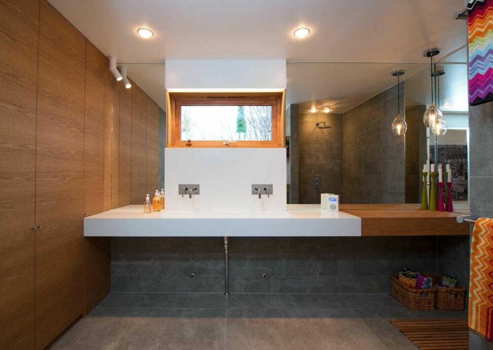 STRAM STIL: De grå flisene på gulv og vegger heter Statale Grigo Cemento og er fra Fagflis. Den justerbare spotten i hjørnet ved skapet heter Mini SCOOP. Den lille teakfuglen til pynt i vinduskarmen er designet av Gunnar Flørning.