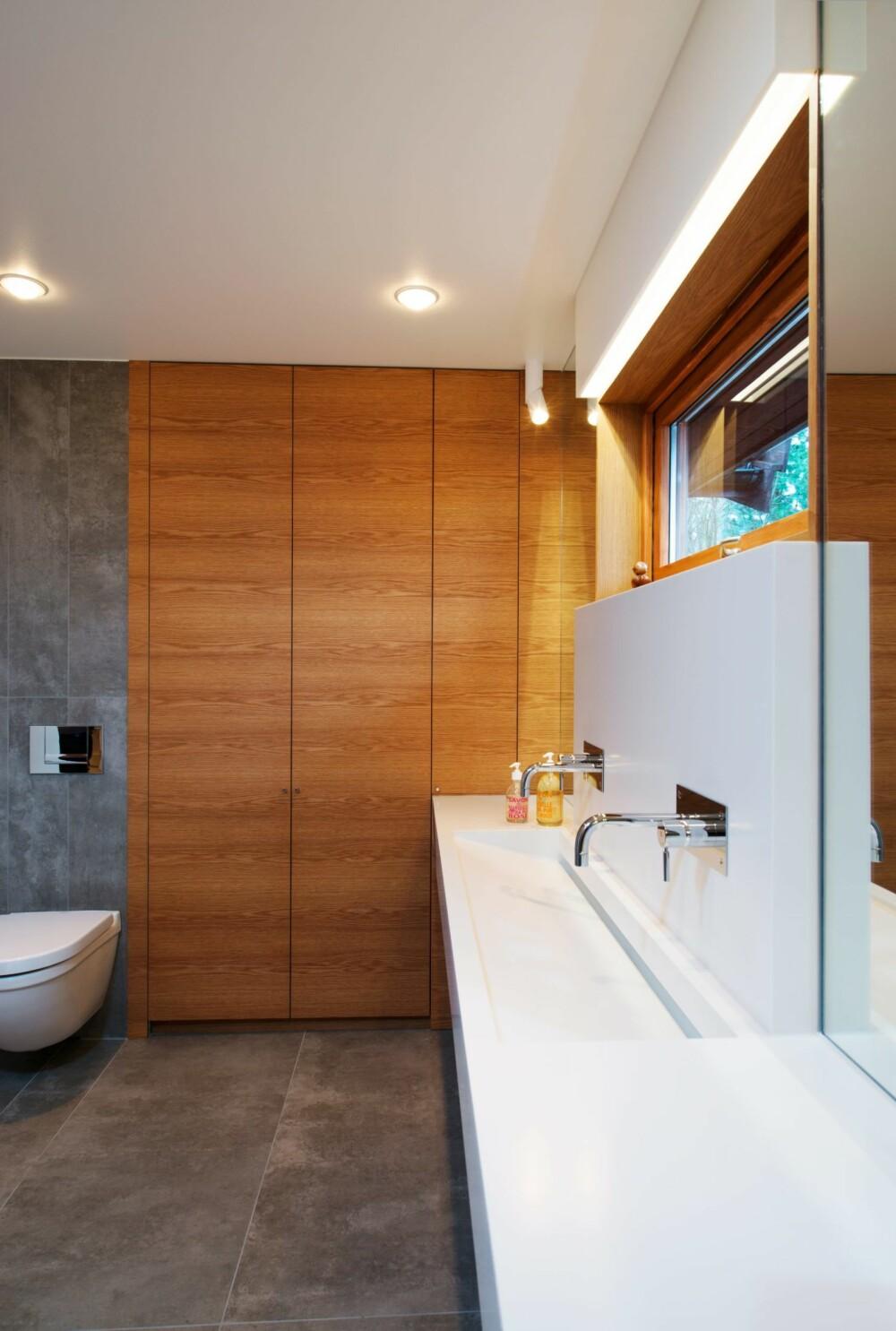 LØSNINGSORIENTERT: Vasken ble flyttet til innsiden av en yttervegg. Denne er for dårlig isolert til å tåle at vannledende rør legges inn i den. Etterisolering ville tatt av rommets areal. I stedet designet interiørarkitekten en pen armaturkasse som holder rørløsningen inne i rommet. Det var derfor ikke nødvendig å ta hensyn til veggtykkelse og isolasjon. Vasken og armaturkasse er i Corian. Det samme er lyskassen over vinduet. Skapene har Svein montert selv, de er i eikefinert MDF, produsert av Jøndal & Hoff, se jondaloghoff.no. Rørlegger-, elektriker- og flisleggerarbeid er utført av Mellem og Martinsen.