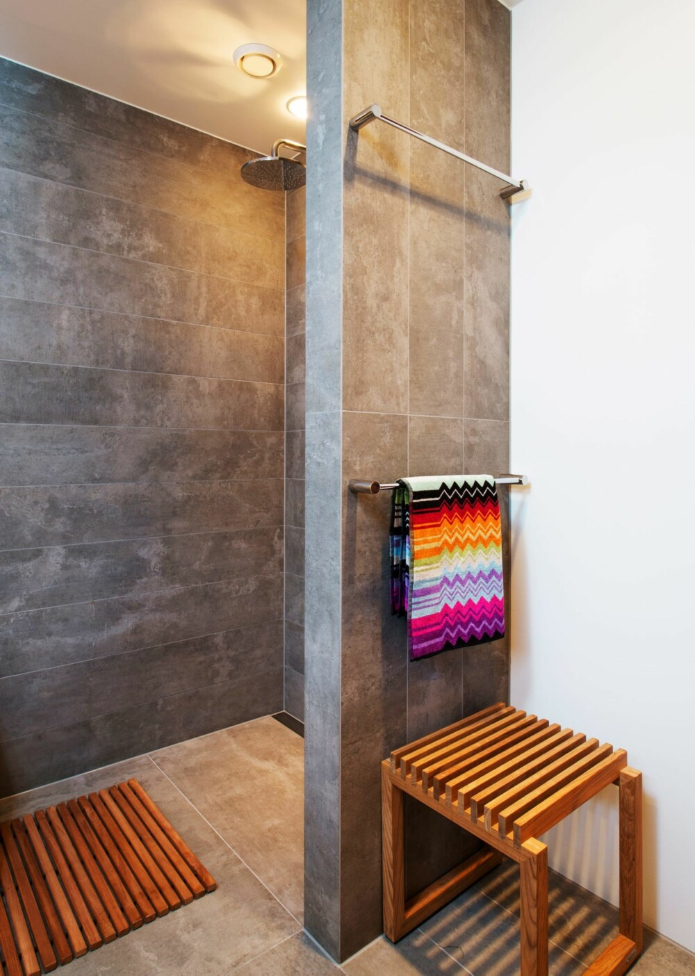 VEGGVARME: I stedet for å montere elektriske håndkletørkere på veggen, er det montert varme direkte i veggen. Håndklærne er fra Missoni. Trekrakken er fra Skagerak. Badematten i teak er fra en tidligere kolleksjon hos Living.