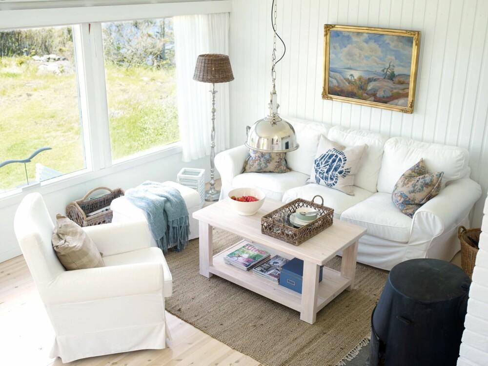 LYST OG HVITT: Stuen på nivå 1 sett fra frokostkroken. Alt av fast interiør er holdt i hvitt så detaljene og maleriet får skinne.