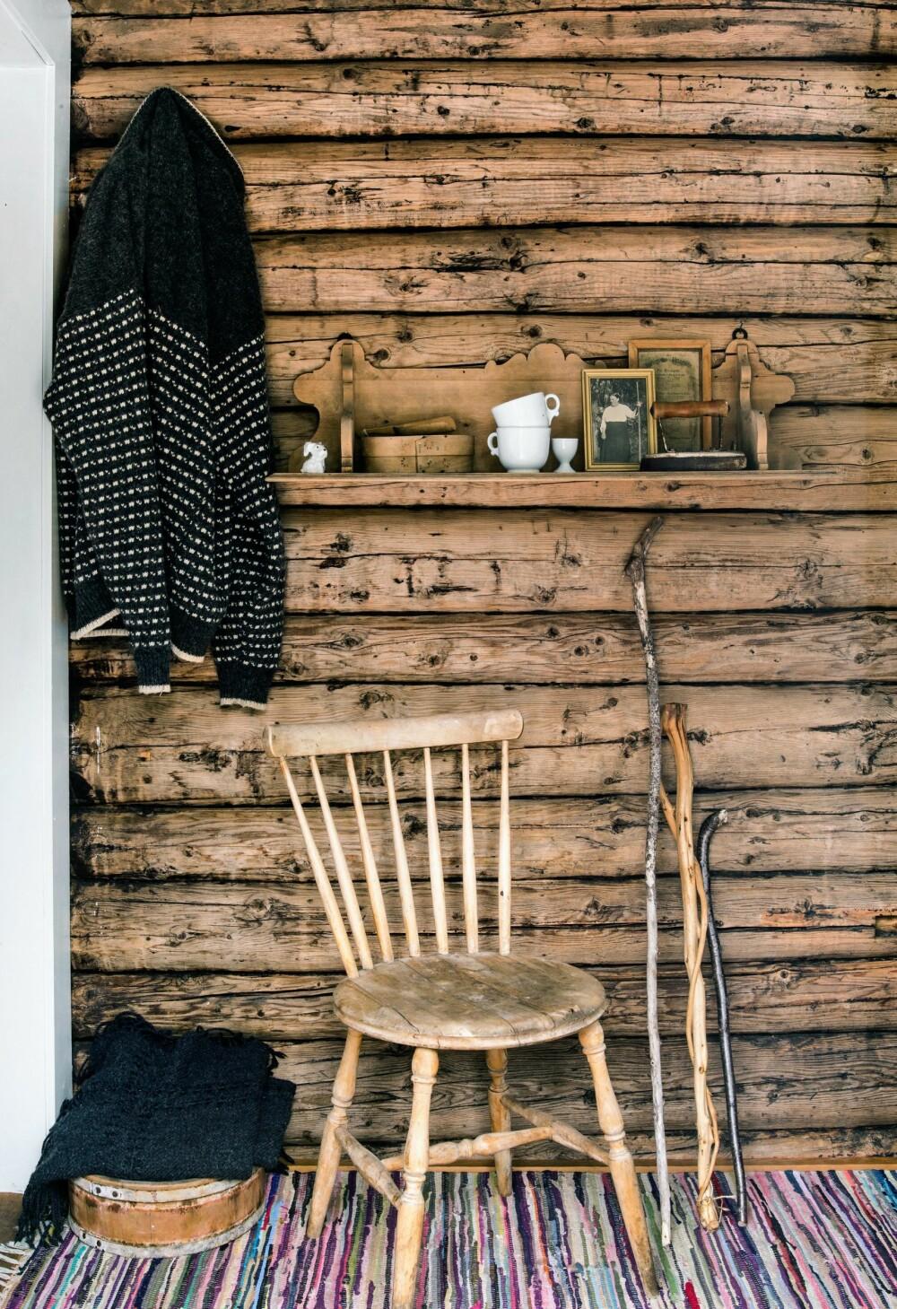 VELKOMMEN: Utenfra kommer en rett inn på kjøkkenet.  Til venstre er stuedøren og på veggen henger en hylle med gamle minner fra livet i skogen. Tømmerveggen er den  gamle ytterveggen fra svalgangen som ble kjøkken.