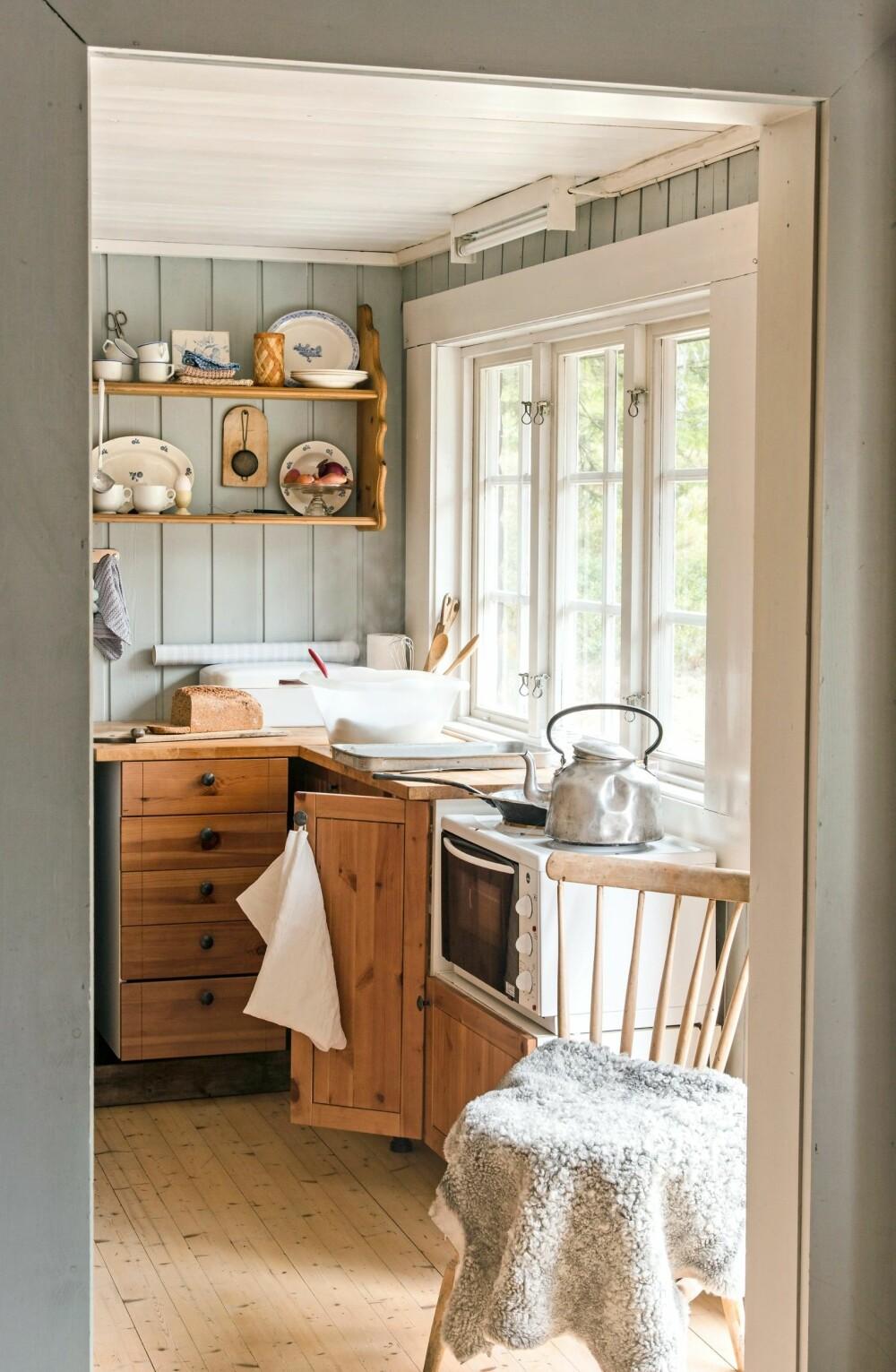 LITE OG KOSELIG: Kjøkkenet i den gamle svalgangen  er ganske smalt, men lyst og fint med store vinduer og hyggelig utsikt ut over tunet. Hytta har strøm,  slik at det er enkelt å sette på en kaffekjele.  Vann må hentes i brønnen på tunet.