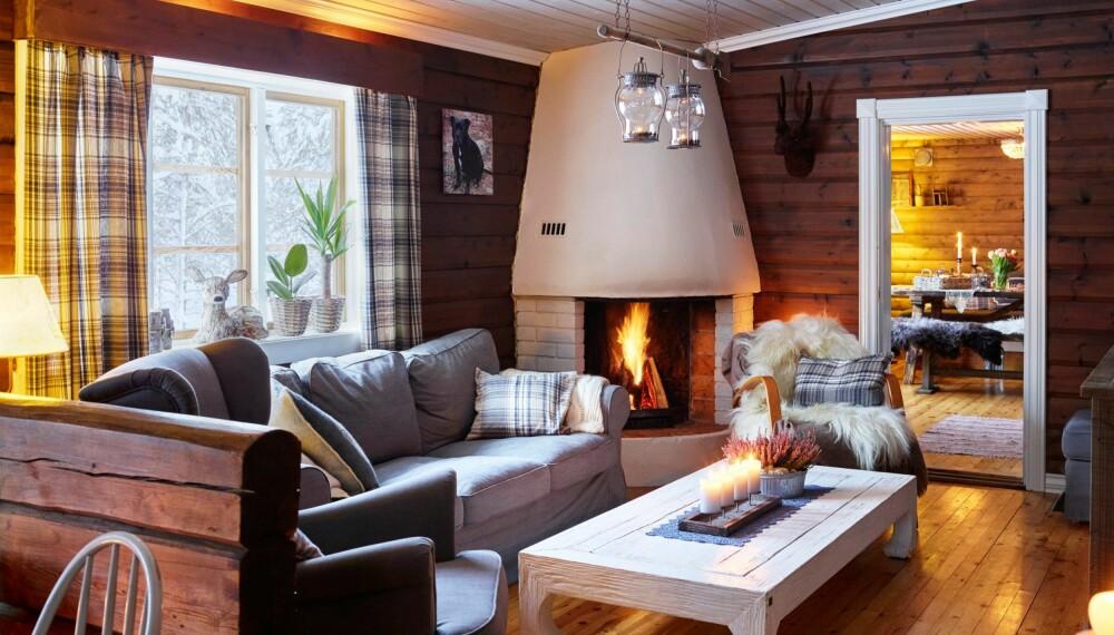 MIDTPUNKT: Den store peisen er sentral i stuen. De beisede veggene luner, mens hvite karmer og lyst tak gjør at helhetsinntrykket ikke blir for mørkt.