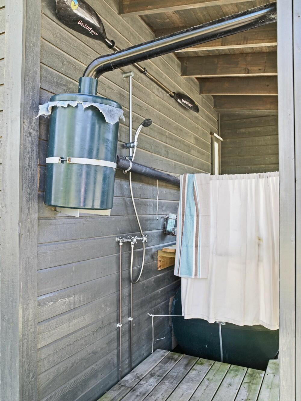 DUSJLØSNINGEN: Utedusjen er montert med trykkstyrt pumpe fra sisternen. En gardin med maljer gir nødvendig avskjerming. Foto: Inger Mette Meling Kostveit