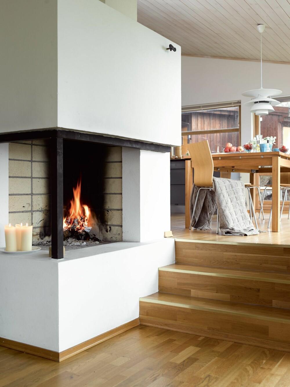 ROMSKILLE: Peisen danner et naturlig skille mellom stue og kjøkken.