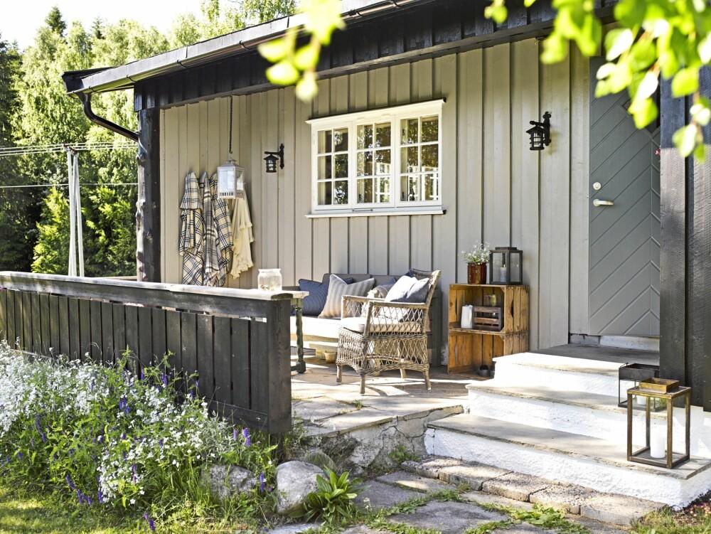 LYSERE: Hytta fikk en ny start med nye farger både utvendig og innvendig. Innhuket i fasaden ved inngangspartiet ble malt lysere enn resten av de utvendige veggene. Uteplassen er møblert med nye puter i sofaen. To utelamper og knagger til pleddene bidrar også til koselige kvelder på terrassen. Innhuket i fasaden ved inngangspartiet: Jotun Svolvær, Drygolin Ultimat. (FOTO: Per Erik Jæger)