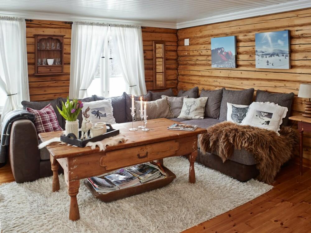 Gammelt og nytt: Sofaen er det eneste som er kjøpt nytt i stuen. Tømmerveggene fra 1800-tallet har fått en fin glød etter at Øystein slipte dem ned.