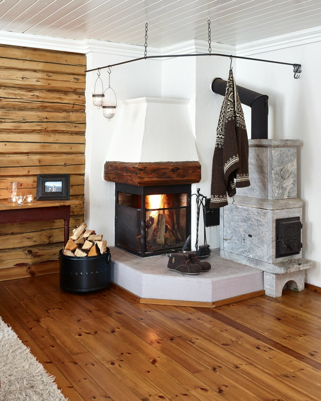 Kos og varme: Peisen og den gode klebersteinsovnen er hjertet i stuen. Jernstangen med kroker er praktisk å tørke våte klær på.