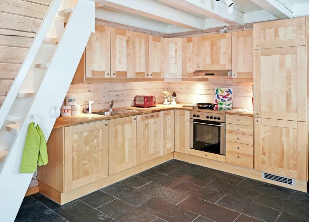 ÅPEN LØSNING: Kjøkkenet fra Ikea har åpen løsning mot stuen. Taket og trappen opp til hemsen er malt i hvitt for å gi hytta et lysere uttrykk. FOTO: Sveinung Bråthen.