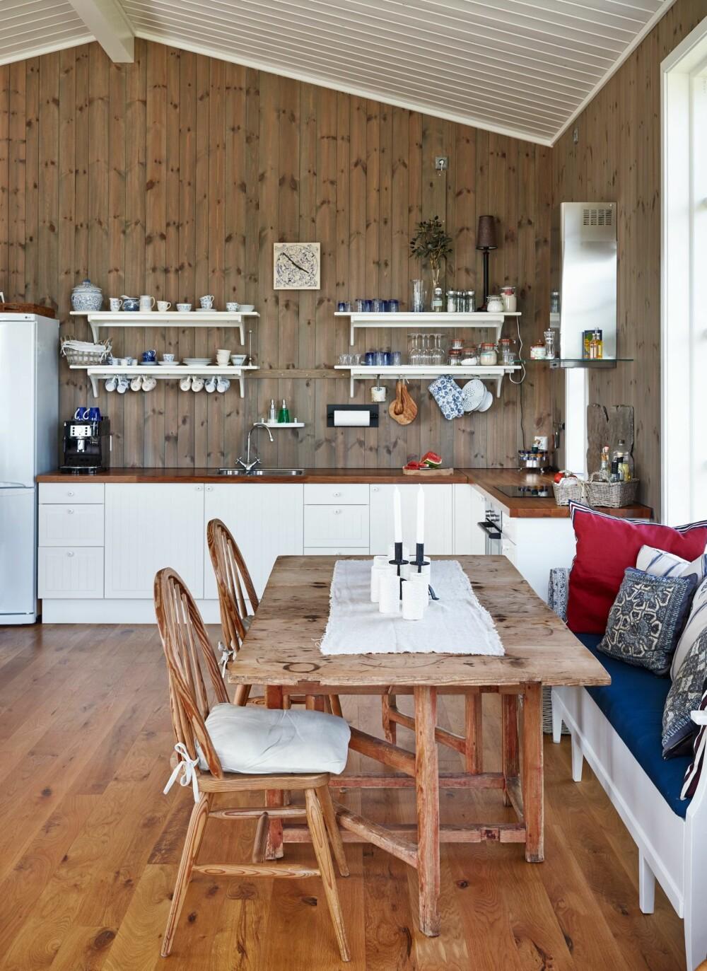 MØBLER MED HISTORIKK: Spisebordet er kjøpt hos en brukthandler i 1985 og har fulgt familien siden. Stolene er fra Falk Møbler i Drammen og benken ble kjøpt via en nettannonse. Det var vanskelig å finne en slagbenk som passet på en sommerhytte. Denne kom fra Sverige og var litt sliten, men er pusset opp og malt.