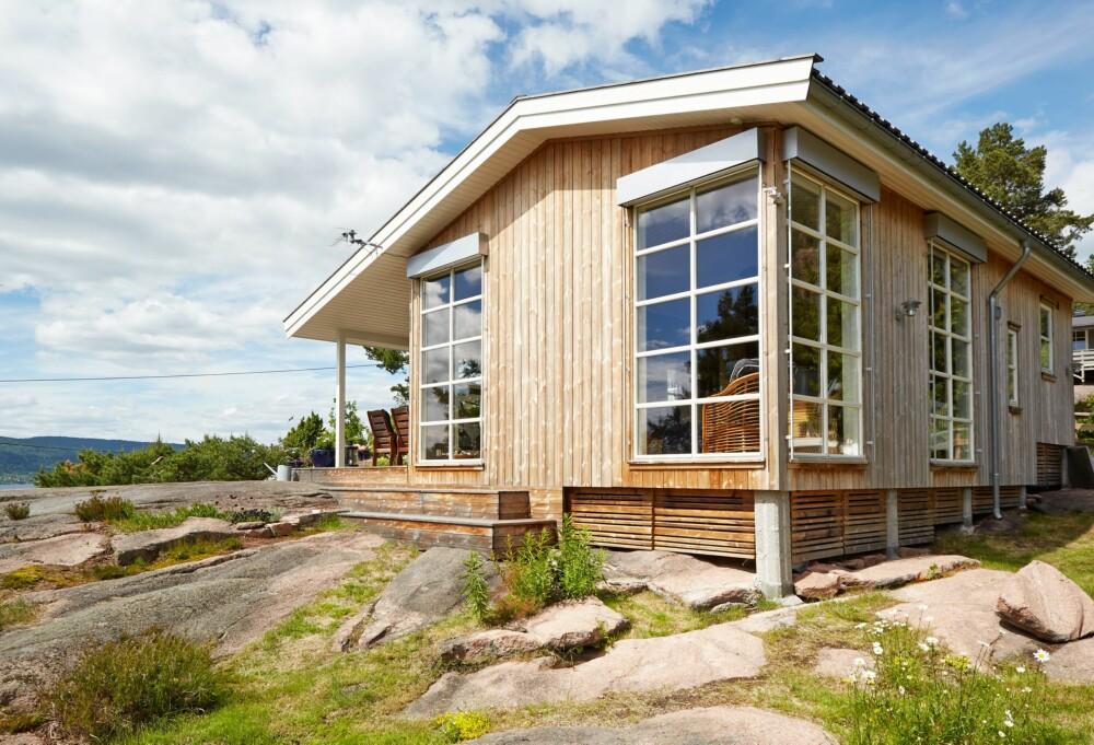 KLER OMGIVELSENE: Valget av Kebony på tak, vegger og terrasser gjør at hytta passer godt inn i terrenget. Vinduene er 2,8 meter høye, og åpner opp for utsikten mot Horten og Oslofjorden.Vinduene har utvendig monterte persienner.