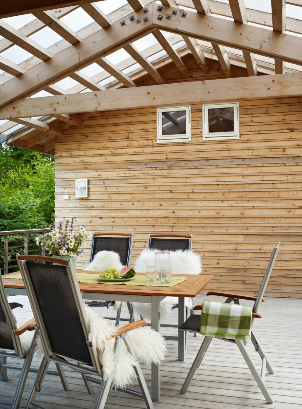 SMART UTEPLASS: Terrassen er hyppig i bruk. Den er overbygget mellom to bygningskropper med pergola som tak. Det gir godt dagslys ned på det som er blitt en populær uteplass