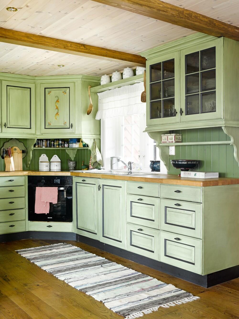 TRADISJONELT KJØKKEN: Kjøkkenet  er selvtegnet av hytteeierne,  plassbygget av en lokal snekker,  og malt i grønt og svart, lasert med brent umbra.
