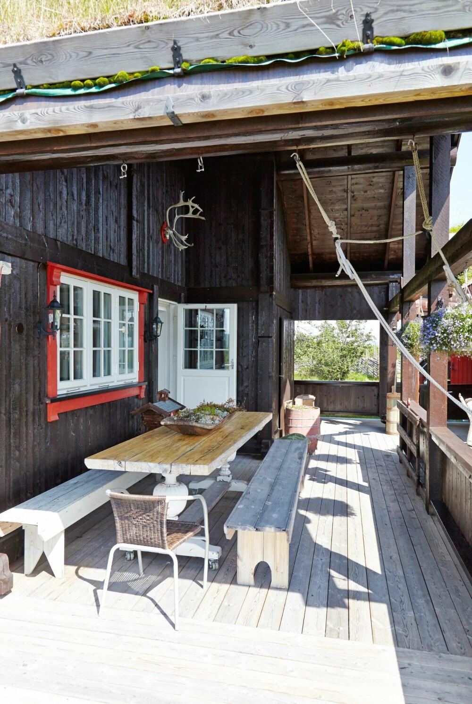 OVERBYGGET TERRASSE: Terrassen med overbygg blir brukt mye, der kan de sitte ute, uansett vær. Eikebordet og benkene er laget av hytteeierne, bortsett fra understellet til bordet som ble kjøpt på loppemarked.