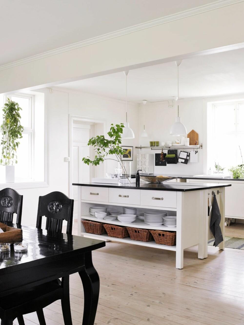 ÅPNET OPP: I taket er restene av en revet vegg. Kjøkkenet er fra Ikea, men malt hvitt. Benkeplater og spisemøblemen er malt med bengalakk, en slitesterk og rimelig behandling. Stoler og bordben er arvet. Pendler fra Louis Poulsen i to størrelser henger over øya og langs veggen. Styling: Kirsten Visdal.