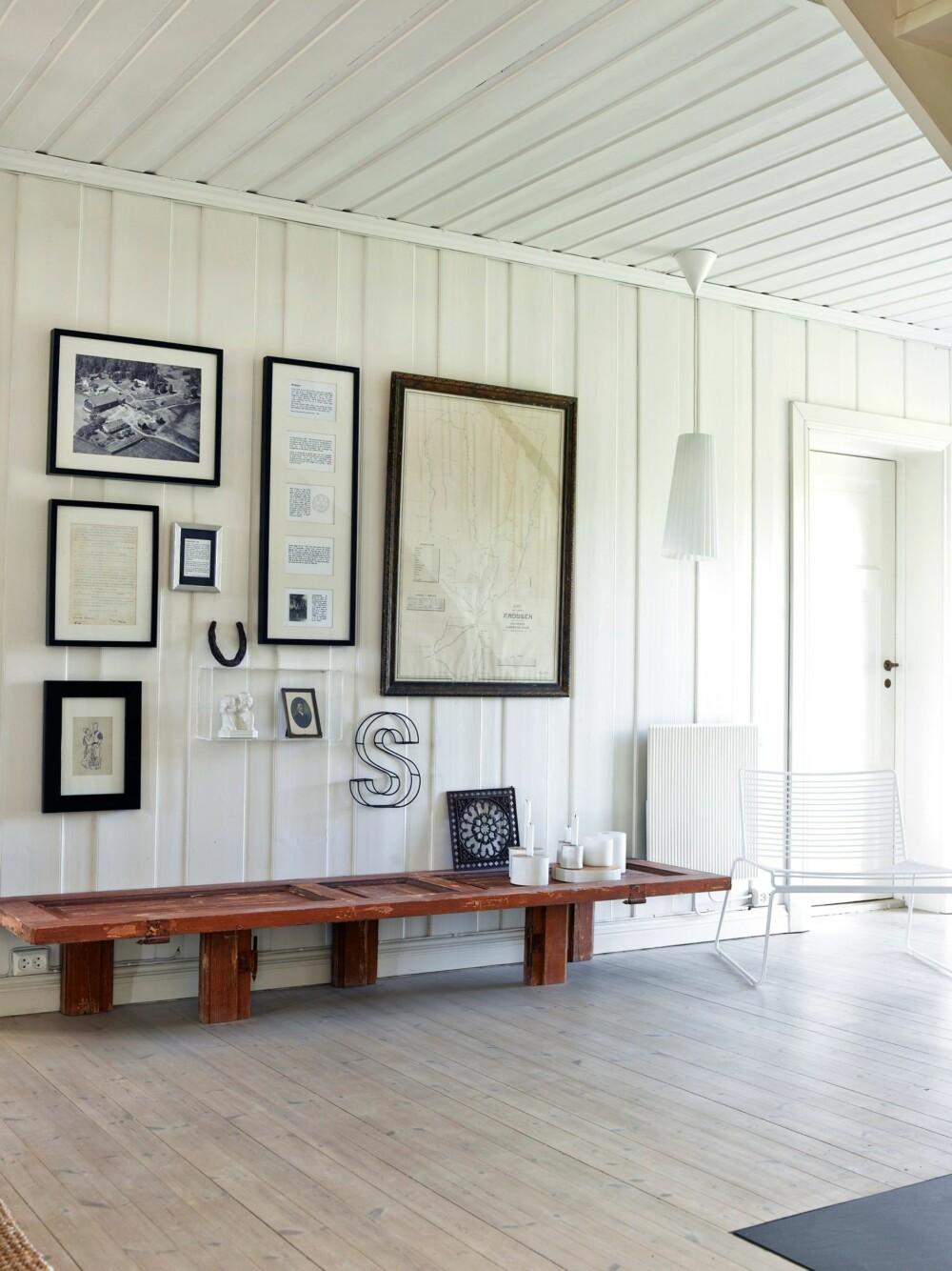GÅRDSHISTORIE: I hallen står en benk laget av den gamle inngangsdøren på gården. På veggen bak henger gamle bilder, kart, en kontrakt og gårdsgjenstander. Styling: Kirsten Visdal.
