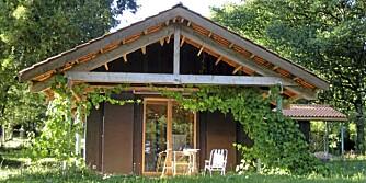 LANDLIG IDYLL I BORDEAUX: Med det store, utstikkende taket blir det god plass til et frodig liv under trærne. Det skjermer både for stikkende sol, regn og vind. Anlegget er tegnet av Harald Høyem, professor i arkitektur ved NTNU i Trondheim. Store skyvepaneler tildekker alt av  vinduer når hytta forlates. Panelte, brunbeisete vegger. Dette er en utmerket base for sykkelturer til hyggelige smålandsbyer og storslåtte vinslott som St.Emilion og Château Lafite-Rotschild.