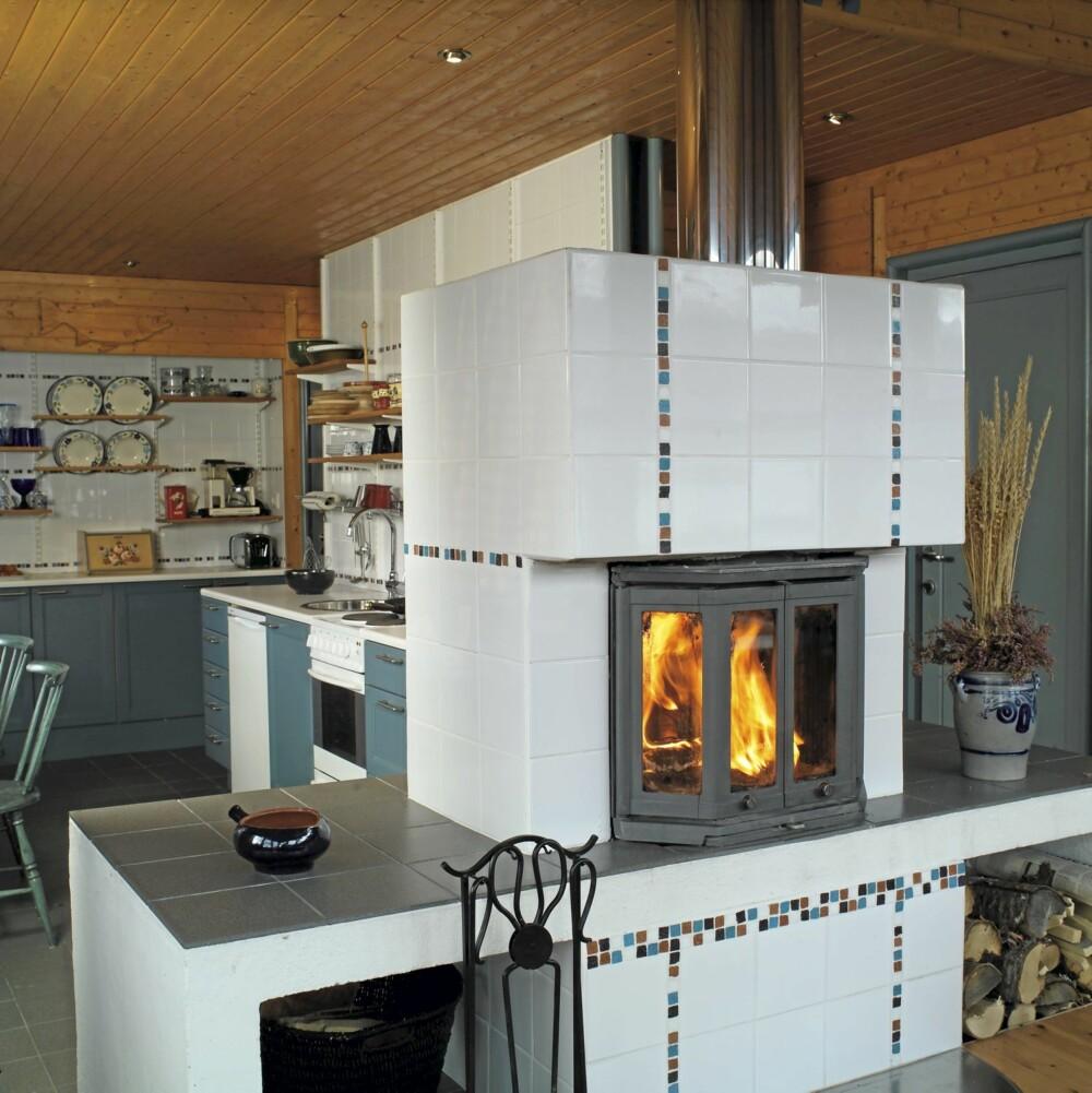 SENTRUM I STUEN: Det store ildstedet midt mellom stue og kjøkken gir både varme og er en effektiv romdeler.