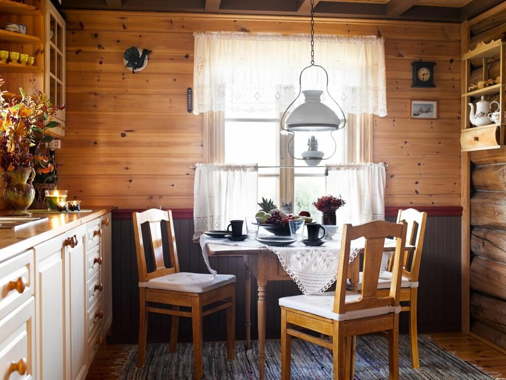 LITEN OG GOD KJØKKENKROK: Ved kjøkkenbordet er det fint å sitte  når maten er underveis på den gamle ovnen, som er bare en håndsrekning unna. Som kontrast er brystpanelet og bjelkene i taket malt mørke.