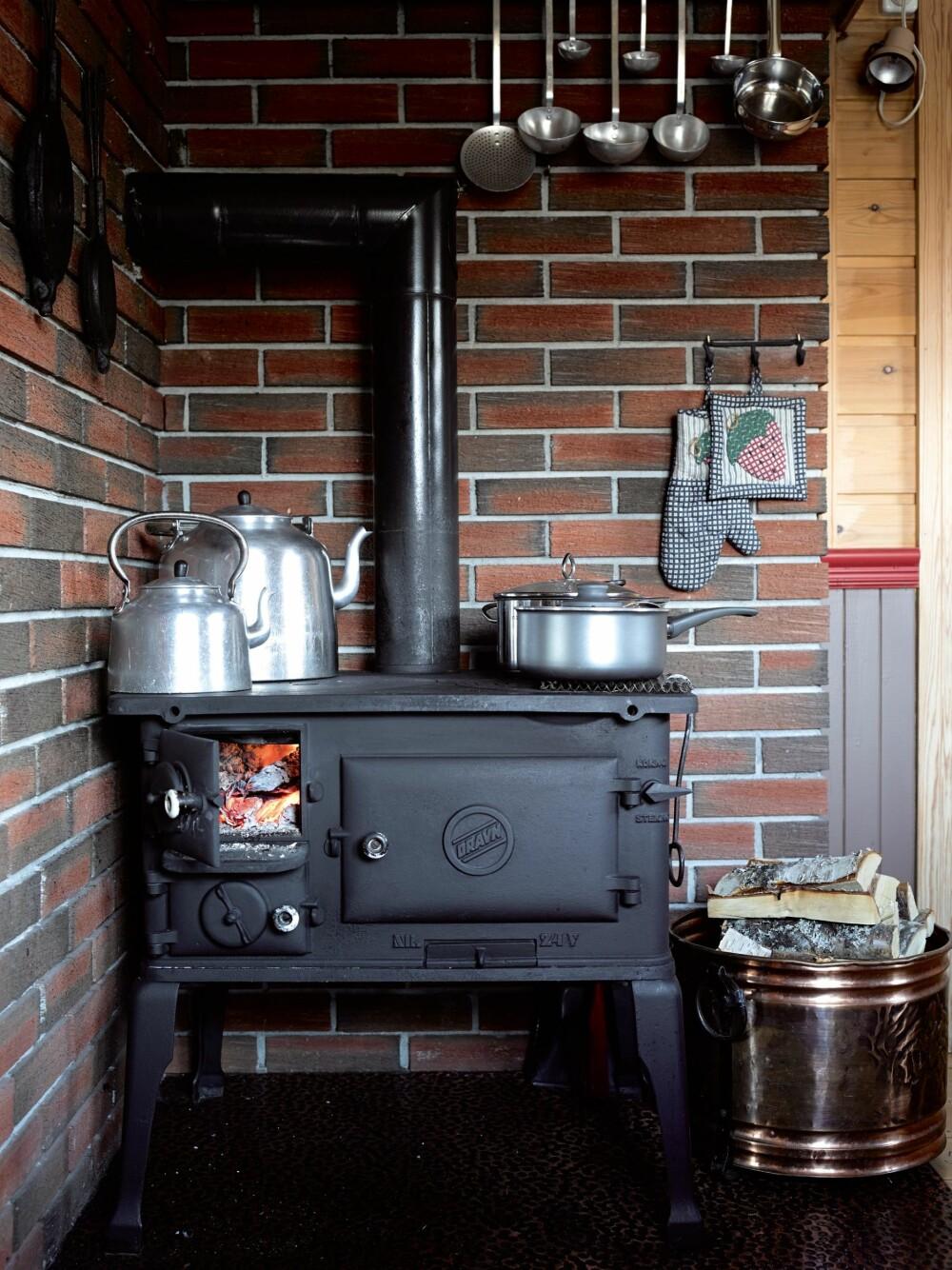 VEDFYRT MATOVN. Den gode, gamle svartovnen er kjøpt brukt i Eresfjord, Nesset kommune. Den tryller Ann Mari frem de beste retter på.