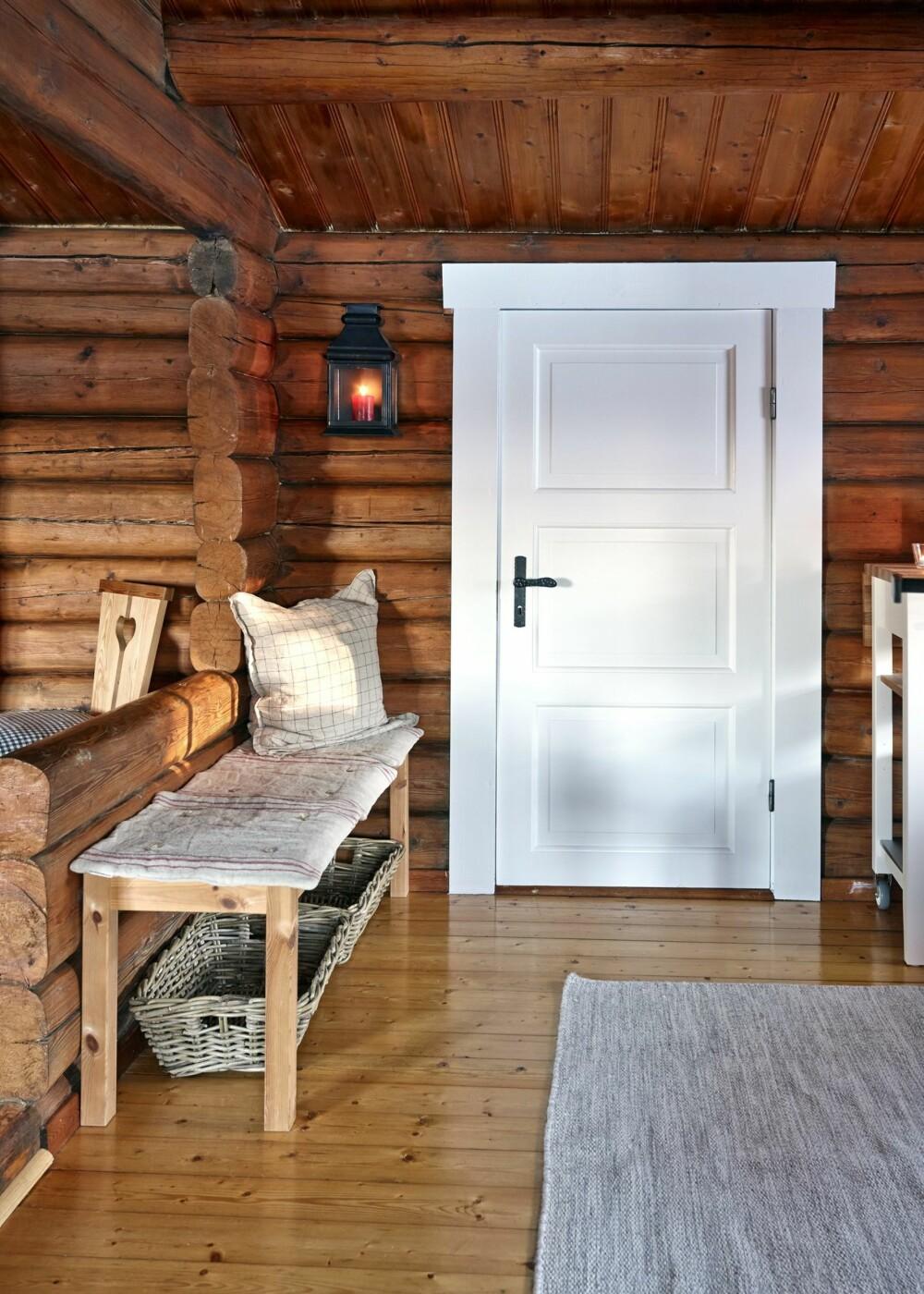 Lun krok: I enden av kjøkkenet, rett ved døren til gangen, er det plassert en hyggelig benk. Den nymalte hvite døren skaper en fin kontrast til tømmeret rundt.