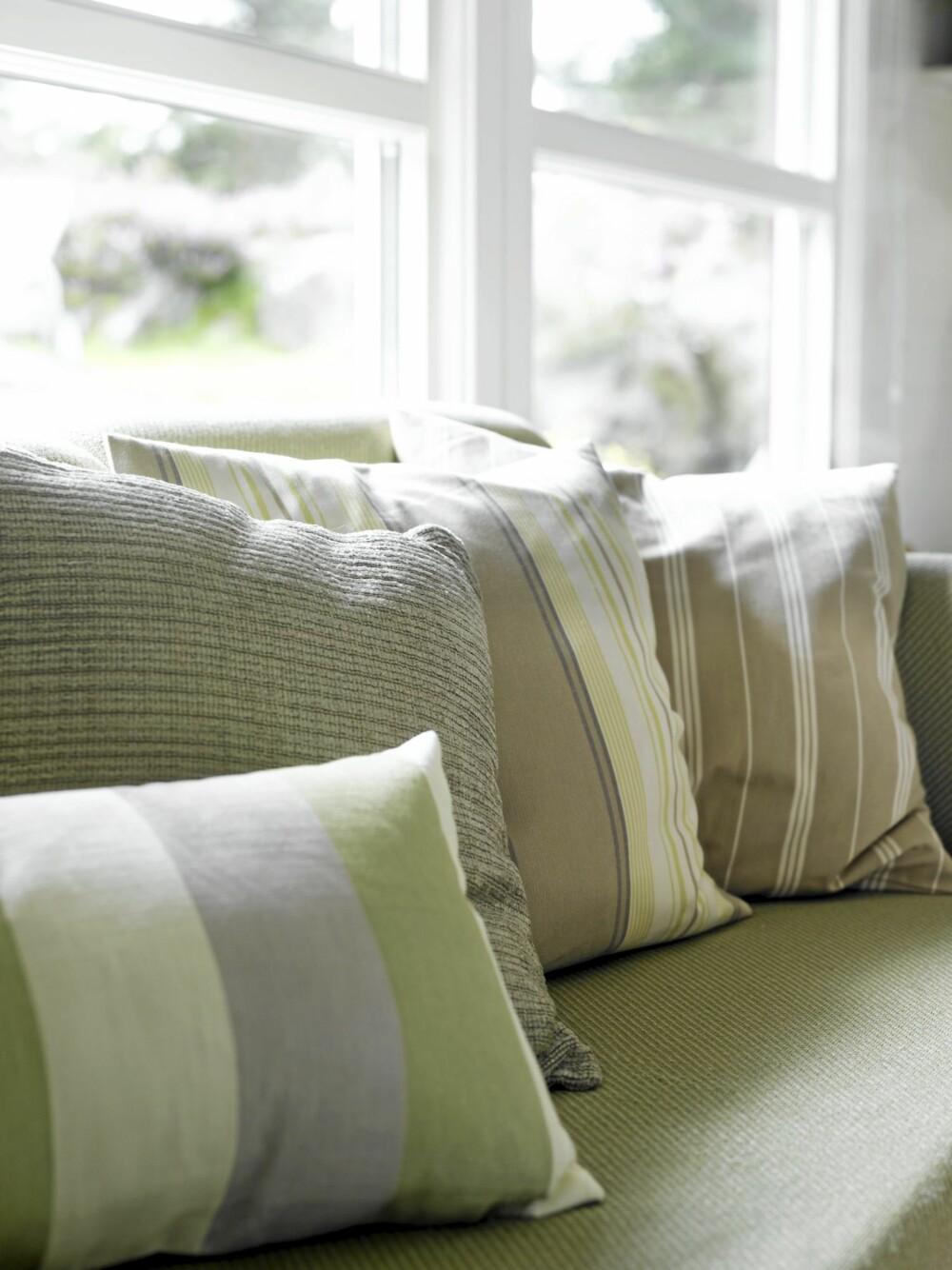 FRISKE PUTER: Sofaen har fått et friskt uttrykk med frodige pynteputer. De to bakerste har Reidun sydd med tekstiler fra Green Apple, mens de fremste er fra Kid interiør.