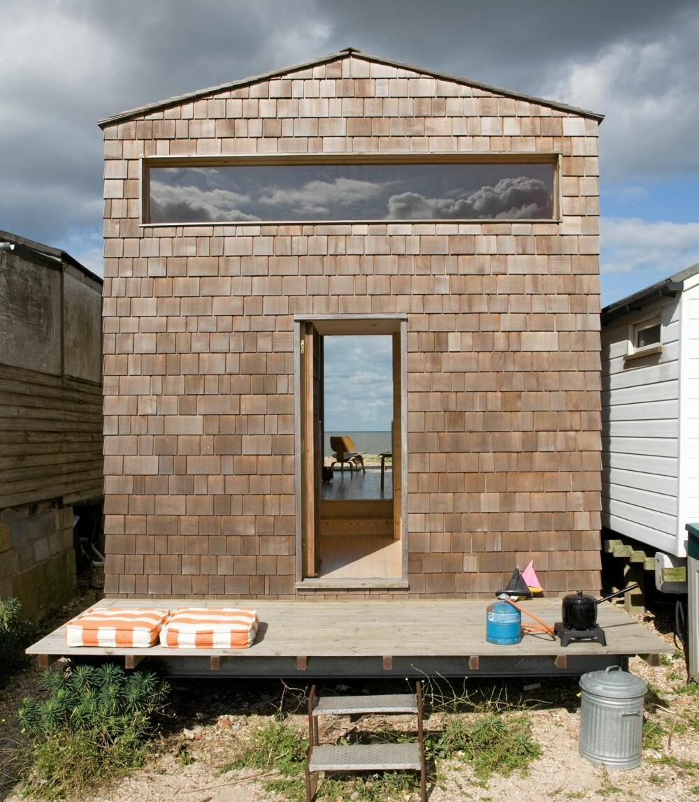GJENNOMGÅENDE: Fra baksiden av hytta ser man rett gjennom til sjøen på andre siden. Det er terrasse på begge sider av hytta.