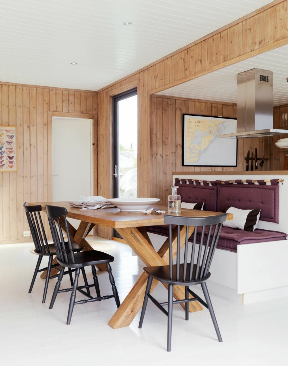 KOMFORT: Baksiden av kjøkkenøya er utnyttet til en sittebenk, tilpasset av lokal snekker i Risør. Spisebordet i solid tre har fått selskap av stoler som er kjøpt på loppemarked og malt i samme farge som på bokhyllene i stuen. Styling: Kirsten Visdal.