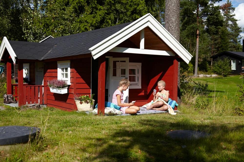 SOLPLASSEN: Hytta ligger godt til rette for sola, og på plenen foran er det ballspill og lek. Terrassen har overbygg, så de kan sitte ute også når det regner.