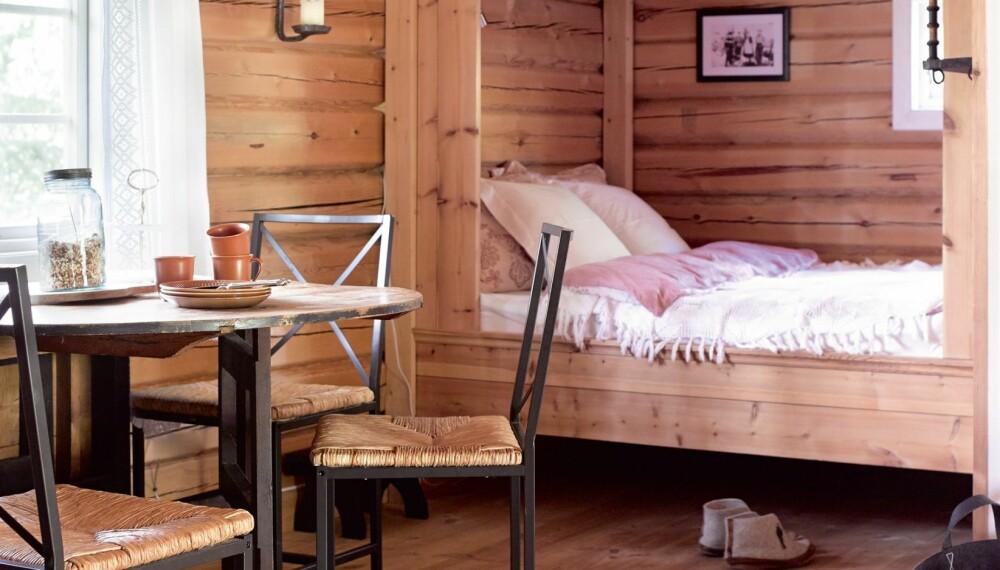 SOVEROM OG KJØKKEN: Sengen på kjøkkenet oppleves som et rom i rommet med den plassbygde innramningen. Ved matlaging settes ytterdøren på vid gap. Stolene er kjøpt via finn.no. Pinnen er et slinn som brukes til å tørke klær over ovnen