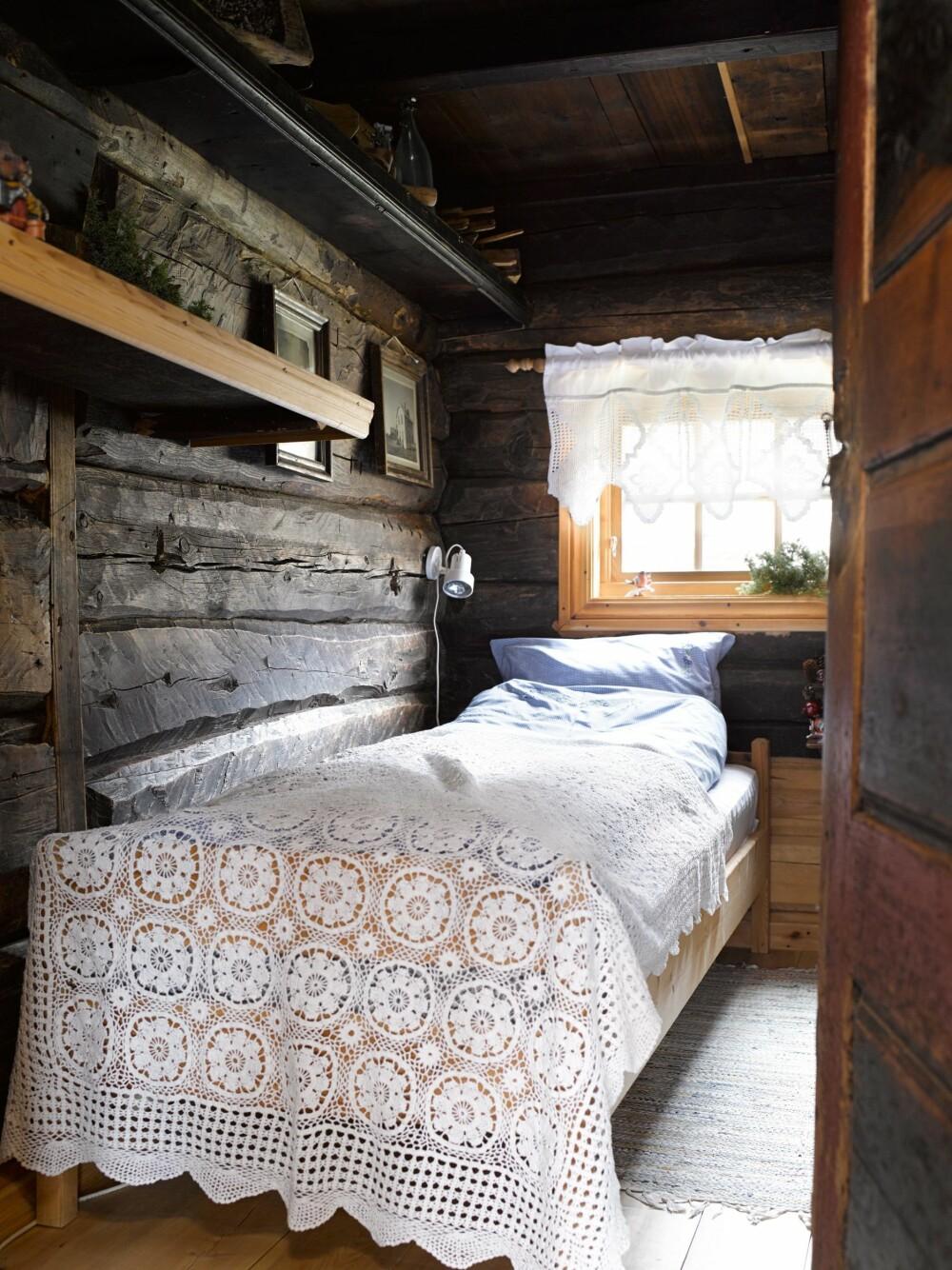 RUSTIKK: De grove tømmerveggene gir liv til soverommet.
