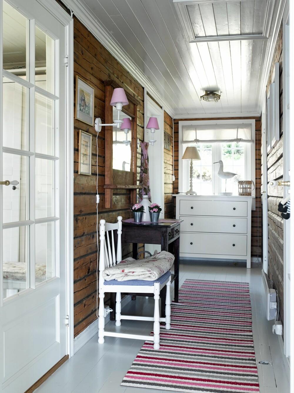 TØMMERET BEVART: I gangen er de originale tømmerveggene fra stabburet hentet frem. Lyse farger ellers fremhever veggene og gjør rommet lyst og trivelig.