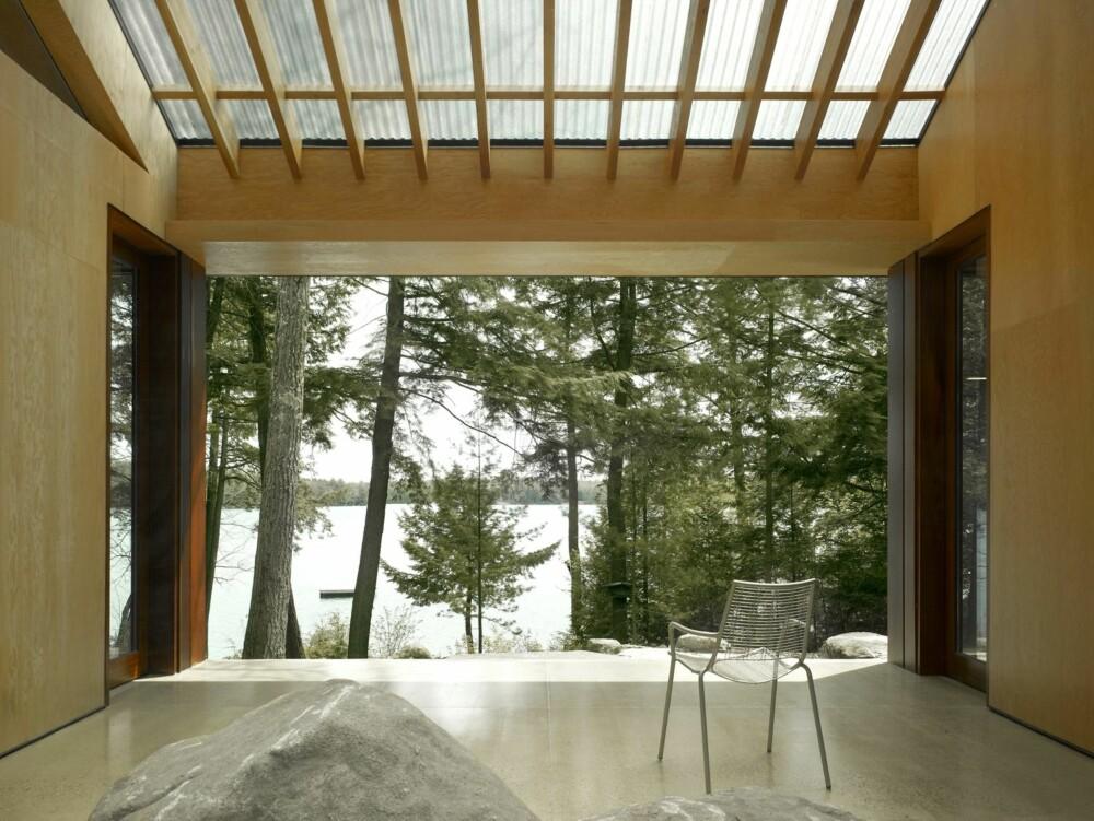 MORGENSTUND: En enkelt stol og en terrasse. Taket og veggene er kledd i kryssfinér av gran.