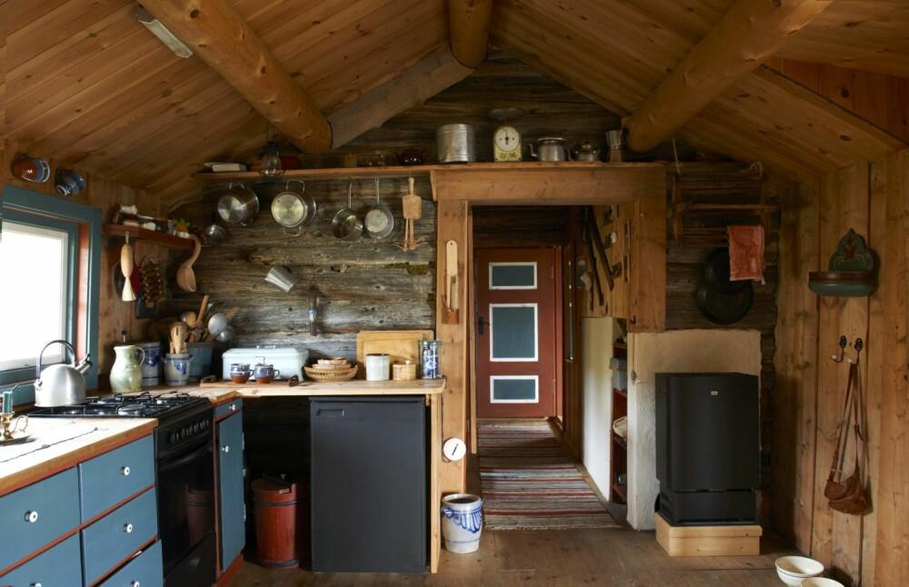 ORIGINALT PREG: Med noen fasiliteter er hytta oppgradert. En fjernstyrt parafinbrenner sikrer en god lunk før Astrid kommer opp. Gasskjøleskap og gasskomfyr gjør kjøkkenøktene noe enklere. Kjøkkeninnredningen er plassbygget av gamle materialer.