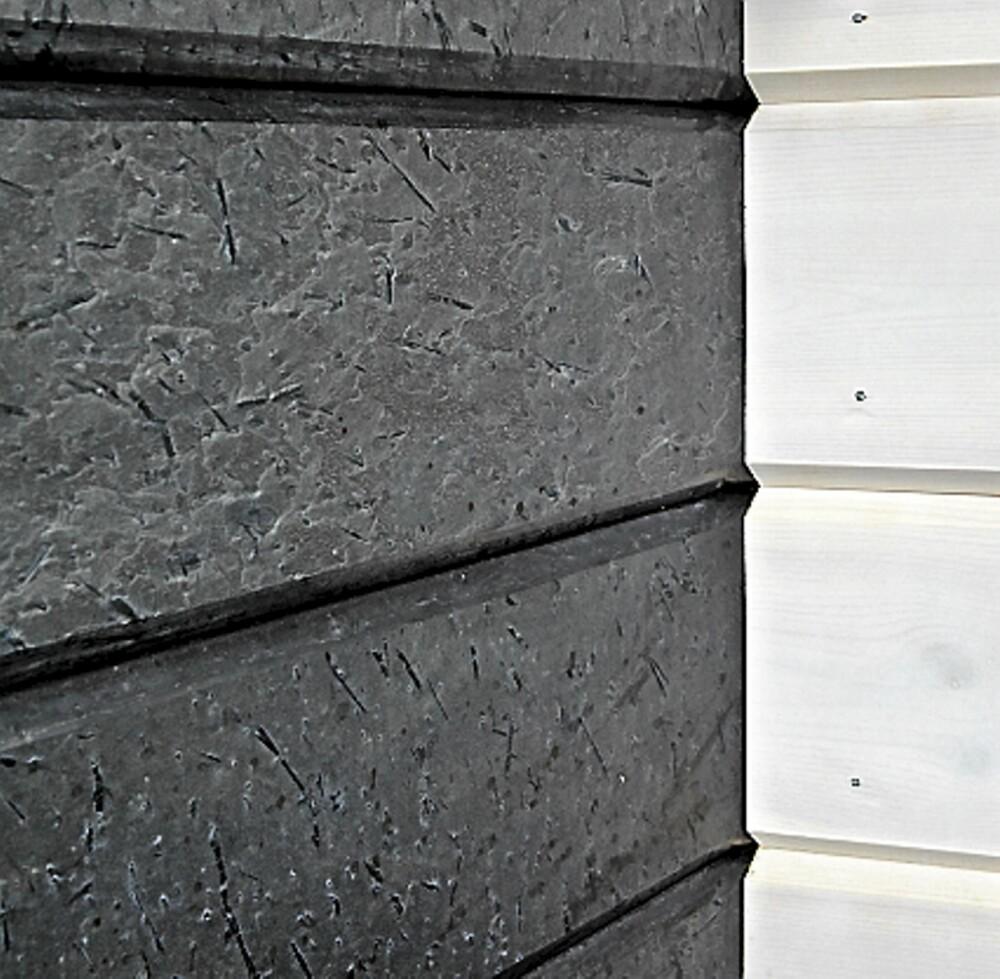 HERLIGE KONTRASTER: Veggene er satt opp med tradisjonelt lyst trepanel, men over kjøkkenbenken glir det vakkert over i børstet ottaskifer.