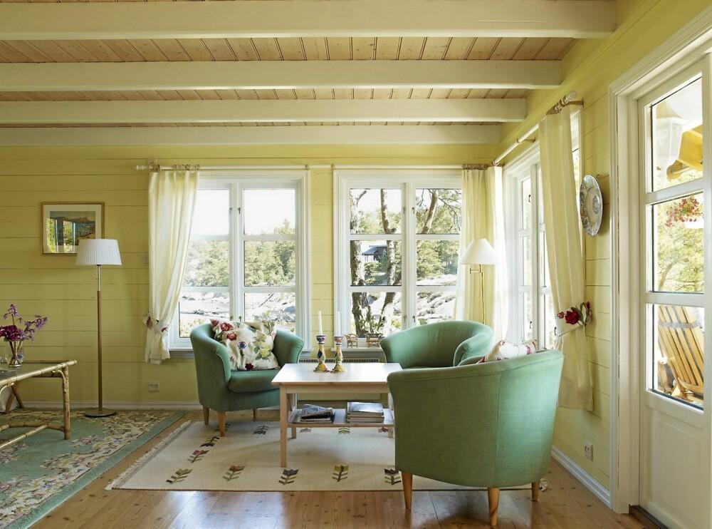 STUA: Hytta er innredet i tandre pastellfarger. Stua er lys gul med hvitlasert tak, hvite bjelker og furugulv. Karmstolene i sommerfargen turkis er kjøpt i Sverige.