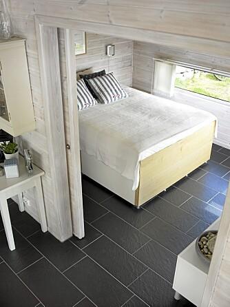 SOVEROM: Foreldrenes soverom ligger på det midterste nivået med en smal vindusrad på to sider. Senga er bygget opp av enkle skapmoduler fra Ikea for å få riktig høyde til vinduene.