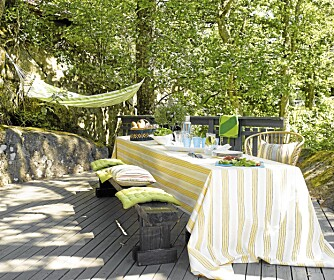 UTEPLASS: På forsiden er det en stor og koselig terrasse. Frodige trær kaster skygge over langbord og benker.