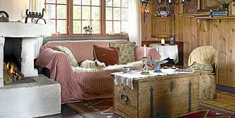 OPPDATERING: Stua har fått en god fjellhyttestemning ¿ lun og koselig, med duse farger og delikat innredning. Eierne har malt det panelte stuetaket mineralgrønt, med listverk i en dypere nyanse. Veggene har beholdt sin opprinnelige farge, gyllent patinert av tidens tann. Det står godt til den dype og komfortable rødrutede sofaen. Det gamle sofabordet er byttet ut med en vakker, antikk kiste fra Rendalen.